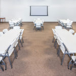 meeting space with 5 tables and 40 chairs and projector screen